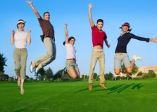Group of young people jumping outdoors grass Royalty Free Stock Photos