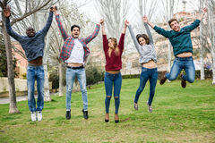 Group of young people jumping together outdoors Royalty Free Stock Image