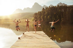 Group of young people jumping into the water from a jetty Stock Images