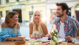 Group of young people laughing in cafe enjoying on sunny day Royalty Free Stock Image