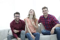 Group of young people laughing and sitting on the couch. Photo with copy space Stock Photo