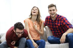Group of young people laughing and sitting on the couch. Photo with copy space Stock Photography