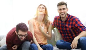 Group of young people laughing and sitting on the couch. Photo with copy space Stock Images