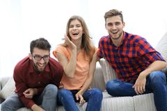 Group of young people laughing and sitting on the couch. Photo with copy space Stock Image