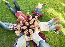 Group of young people laying on the grass, smiling Stock Images