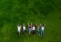 Group of young people laying on the grass, smiling Stock Photography
