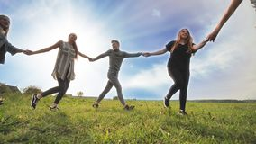 A group of young people lead a round dance holding hands on a summer day. Unity concept.
