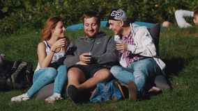 Group of young people lying on bean bags outside, having drinks and laughing. stock video
