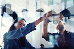 Handshaking business person in office. concept of teamwork and partnership. double exposure with light effects. Group of young people make an agreement in the royalty free stock photo
