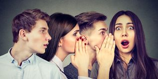 Group of young people men and women whispering each other in the ear. stock photography