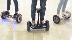 Group of young people are moving around the shopping center on a hyroscooter. Group of young people are moving around the shopping center on a hyroscooter Royalty Free Stock Photo