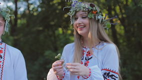 Group of young people in national costumes Slavic celebrate the summer solstice. A group of girls and boys talking and stock video footage