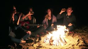 Group of young people near campfire drinking beer and clinking bottles with cheers late at night. Slowmotion shot.  stock video footage