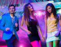 Group of young people at night club. Group of happy young people dancing at night club Royalty Free Stock Image