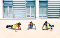 Group of young people performing pushups in modern urban area Royalty Free Stock Photo