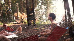 A group of young people playing with a ball in volleyball outdoors in summer forest stock video footage