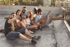Building rooftop selfie. Group of young people playing the guitar, singing and having fun at a rooftop party. Focus on the couple in the middle Stock Photography