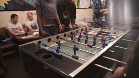 Group of young people playing table soccer in the bar stock footage