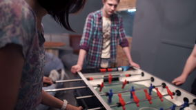 Group of young people playing table soccer in the bar stock video footage