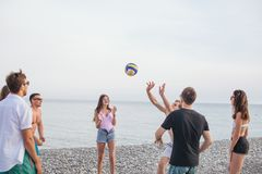 People group have fun and play beach volleyball at summer day. Group of young people playing volleyball on beach royalty free stock images