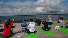 Group of young people practicing in an outdoor yoga class. morning yoga exercises on wooden pier, lake background. Group stock video