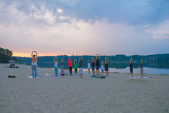 group of young people practicing yoga during the sunrise stock photography