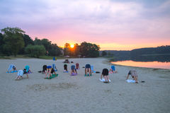 Group of young people practicing yoga during the sunrise. Group of young people practicing yoga on the seaside during the sunrise royalty free stock image