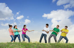 Group of young people pulling a rope. Women against men Royalty Free Stock Image