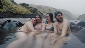 Group of young people relaxing on hot springs in mountains in Iceland. Tourists enjoying the natural spa. Four people in a mountains lagoon, resting after stock video footage