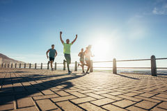 Group of young people running along seaside royalty free stock photo