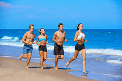 Group of young people running in the beach Stock Images