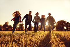 A group of young people running through the grass in the park at sunset. stock photography