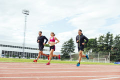 Group of young people running on the track field Stock Image