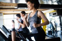 Group of young people running on treadmills in modern sport gym stock photos