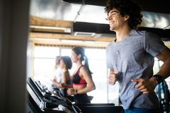 Group of young people running on treadmills in modern sport gym stock photo