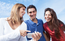 Group of young people showing pictures at phone. With blue sky in the background Royalty Free Stock Image