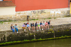 A group of young people sit on  the banks of the Danube. Talking and texting on their smartphones Royalty Free Stock Images