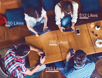 Group of young people sitting at a cafe, counting likes Royalty Free Stock Images