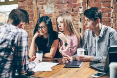 Group of young people sitting at a cafe, drinking coffee and discussing new ideas. royalty free stock photos