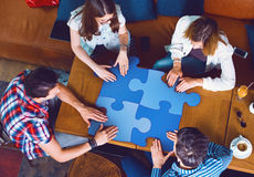 Group of young people sitting at a cafe, holding a puzzle pieces Stock Images
