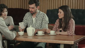 Group of young people sitting at a cafe, talking and drinking tea stock video footage