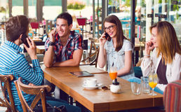 Group of young people sitting at a cafe, talking over phones Stock Photos