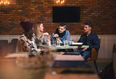 Group of young people sitting in a coffee shop. Having fun Royalty Free Stock Photos