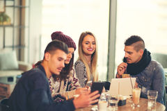 Group of young people sitting in a coffee shop. Having fun Stock Image