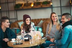 Group of young people sitting in a coffee shop. Having fun Royalty Free Stock Image