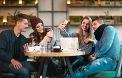 Group of young people sitting in a coffee shop. Having fun Stock Images