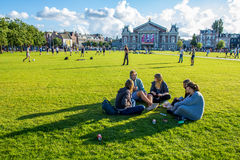 Group of young people sitting on grass in front of Concert gebouw Amsterdam Stock Photo
