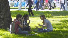 A group of young people sitting on the lawn in the Park stock video