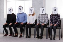 A group of people sitting in chair and on their faces is a sheet of paper with a question mark. Indoors. stock image