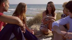 Group Of Young People Sitting On The Sandy Beach. Young gang of five people sitting on the sandy beach and enjoy leisure time on the beach while discussion stock video